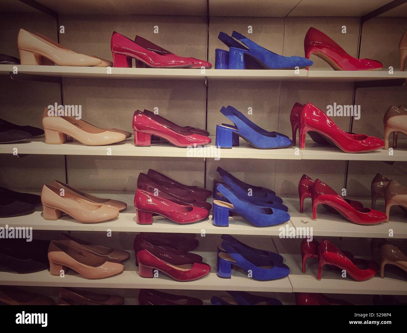 A display of shoes lined up in rows on shelves in a shop. - Stock Image