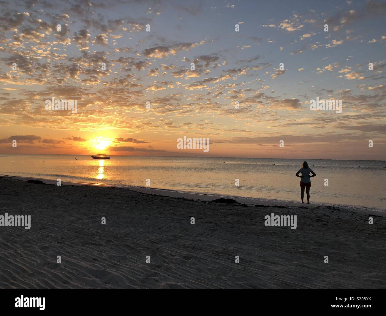 Woman standing on beach looking at Mexican sunrise - Stock Image