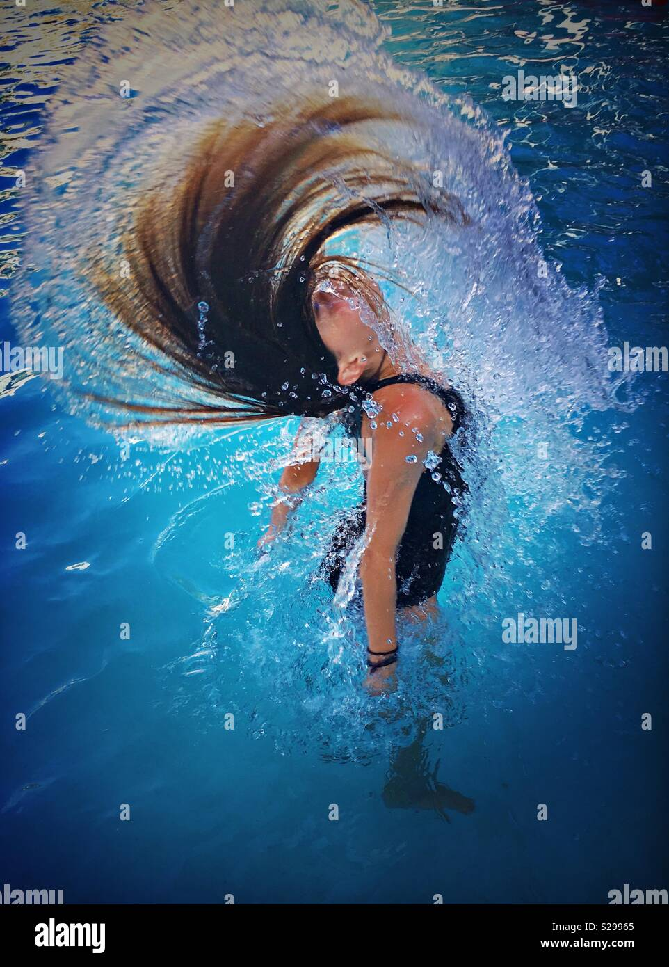 Girl flipping hair in water in pool. - Stock Image
