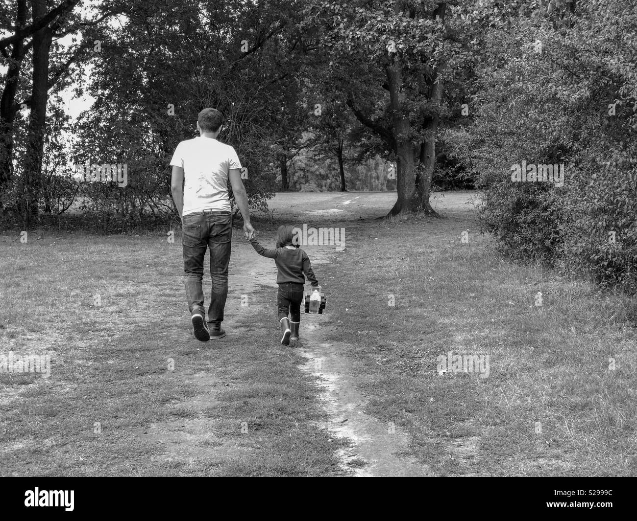 Father and daughter holding hands on a road in a park - Stock Image
