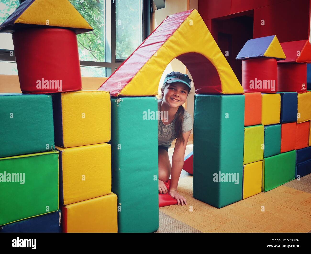 11 year old girl peeking through doorway of large block castle at an indoor play area - Stock Image