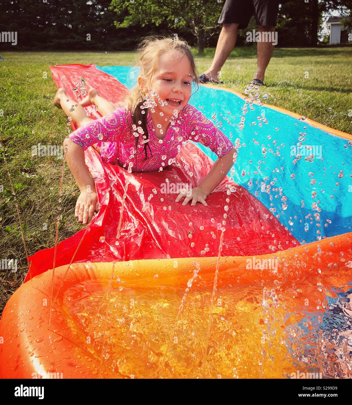 6 year old girl sliding down plastic water sprinkler slide toy outside - Stock Image