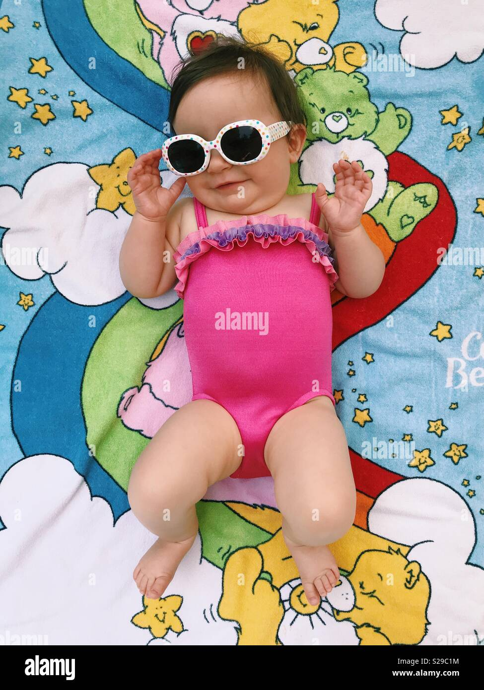 A cute baby girl in a pink bathing suit, wearing sunglasses and lying on a Care Bears beach towel. - Stock Image