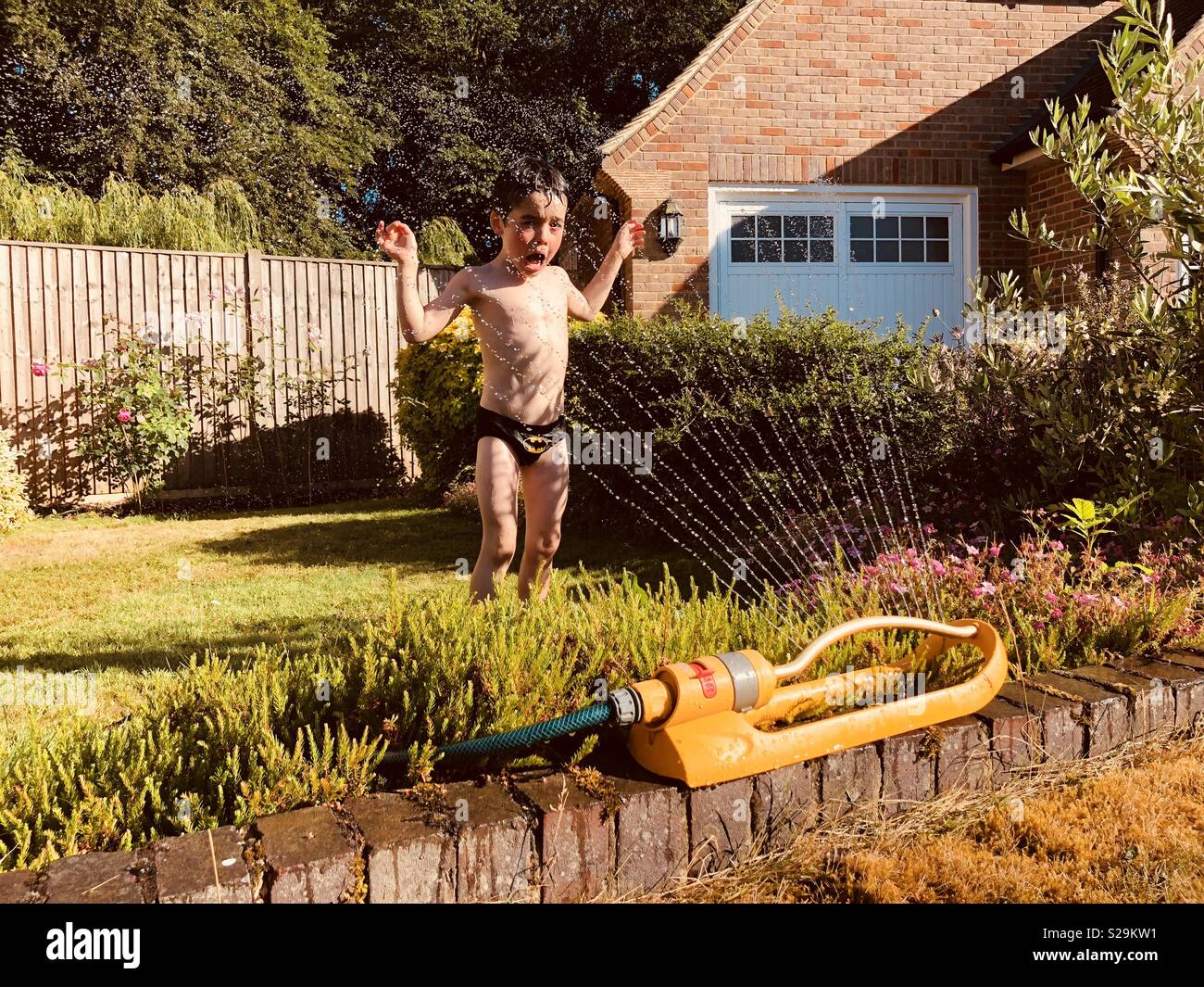 Boy sprayed by sprinkler in hot weather - Stock Image