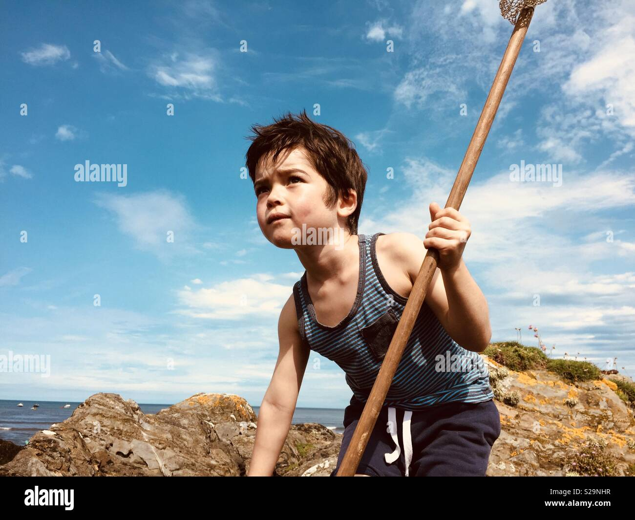 Boy in search of adventure by the sea - Stock Image
