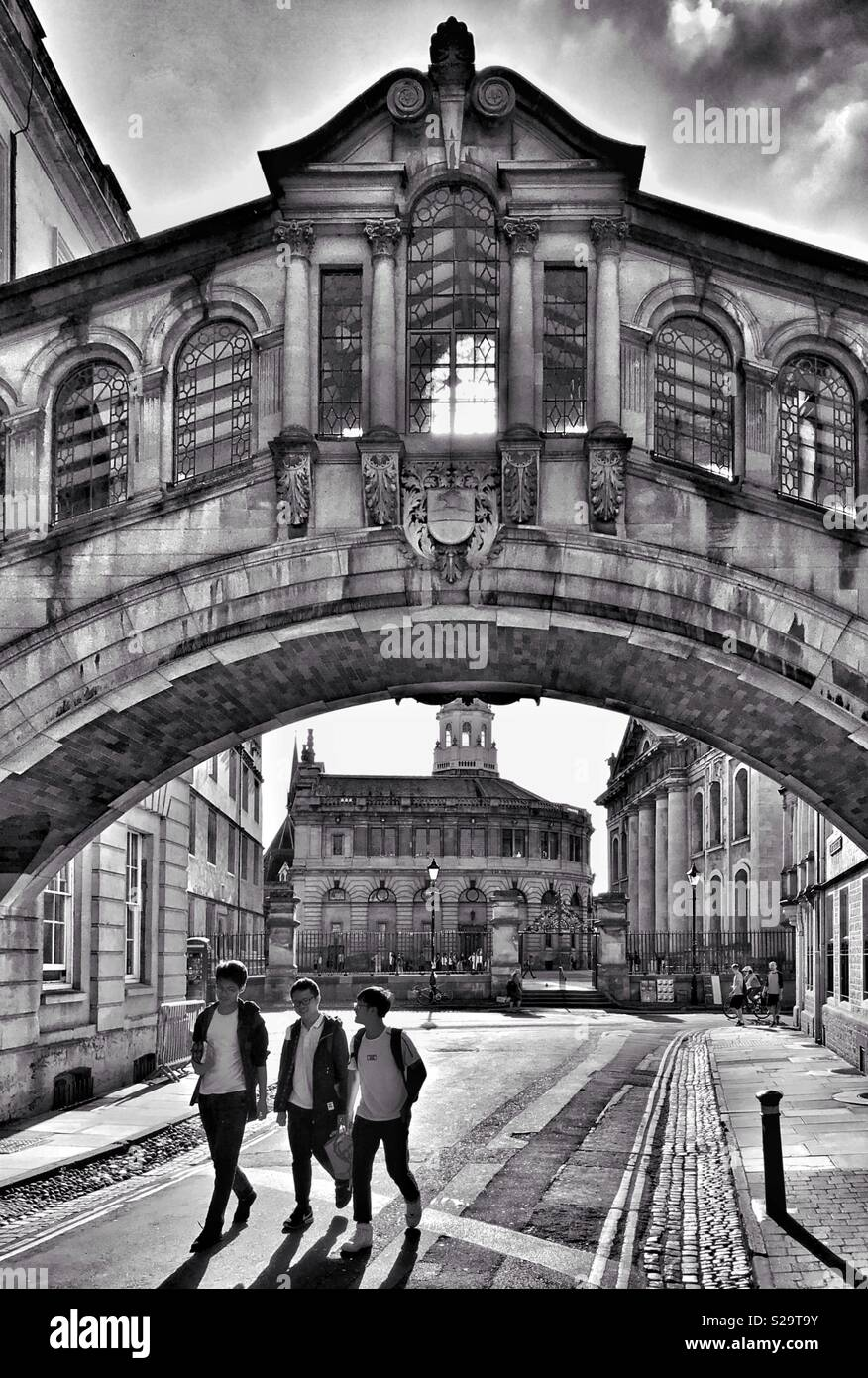 "Three friends walk underneath the famous ""Bridge Of Sighs"" in Oxford, England. The famous Hertford Bridge landmark links the Old & New Quadrangles Of Hertford College. Photo Credit - © COLIN HOSKINS. - Stock Image"