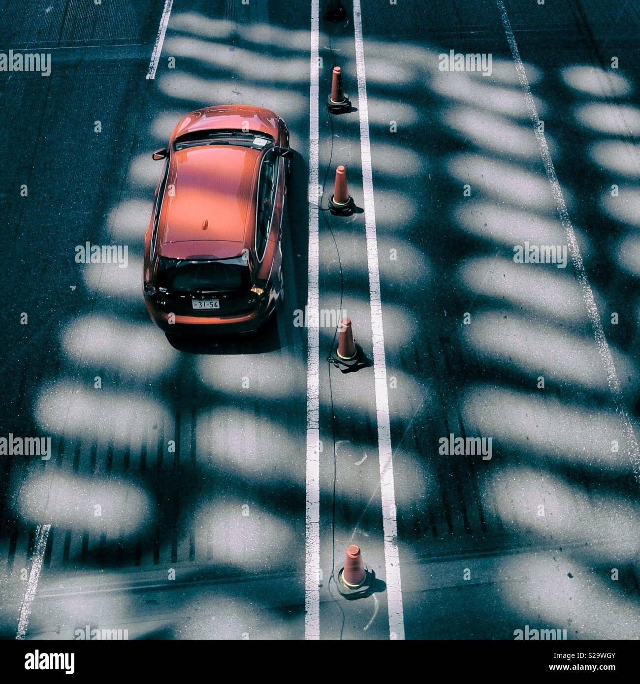 A red car passes road cones and shadows. Overhead perspective - Stock Image