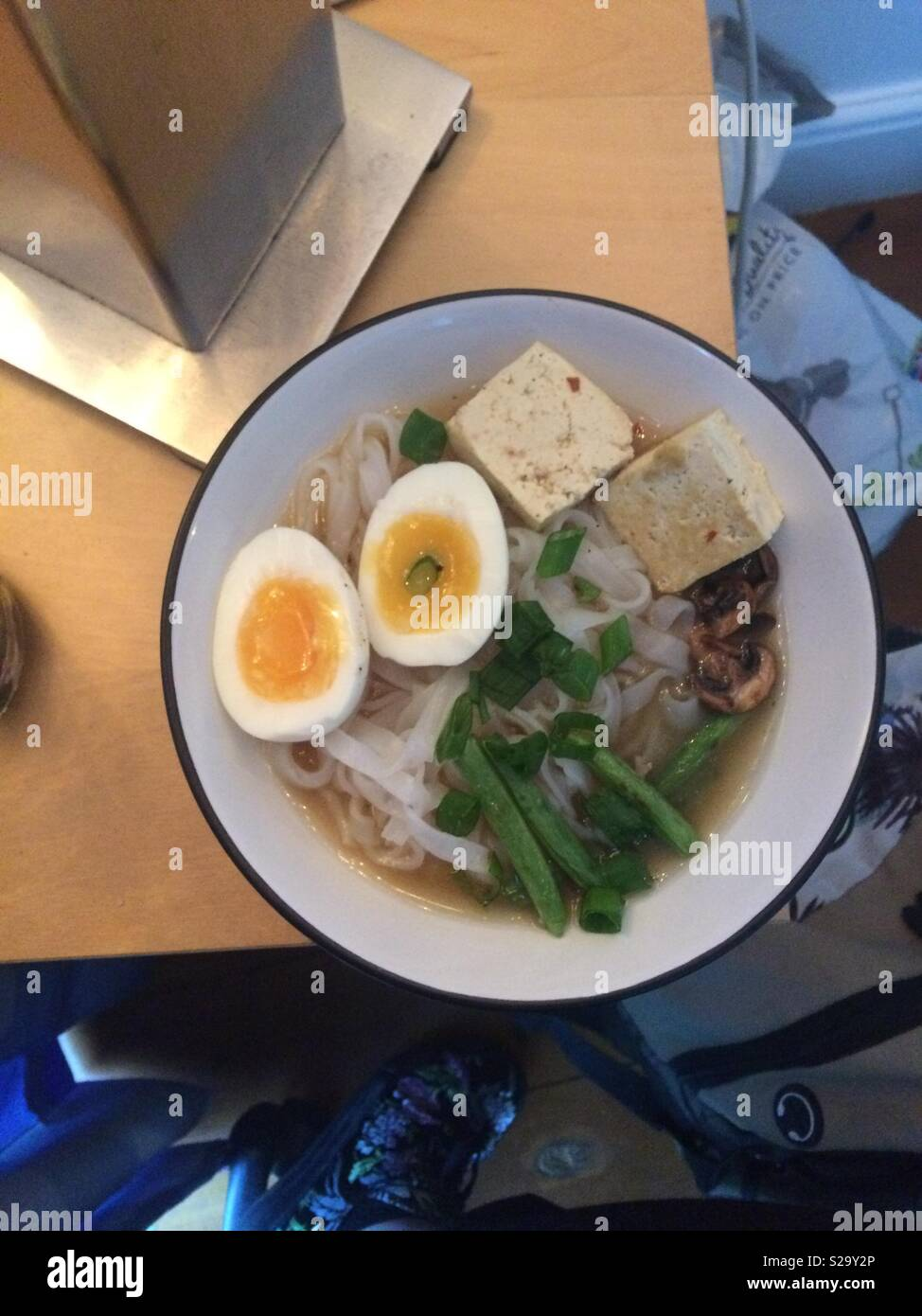 Homemade miso soup topped with tofu, rice noodles, greens, and a boiled egg. - Stock Image