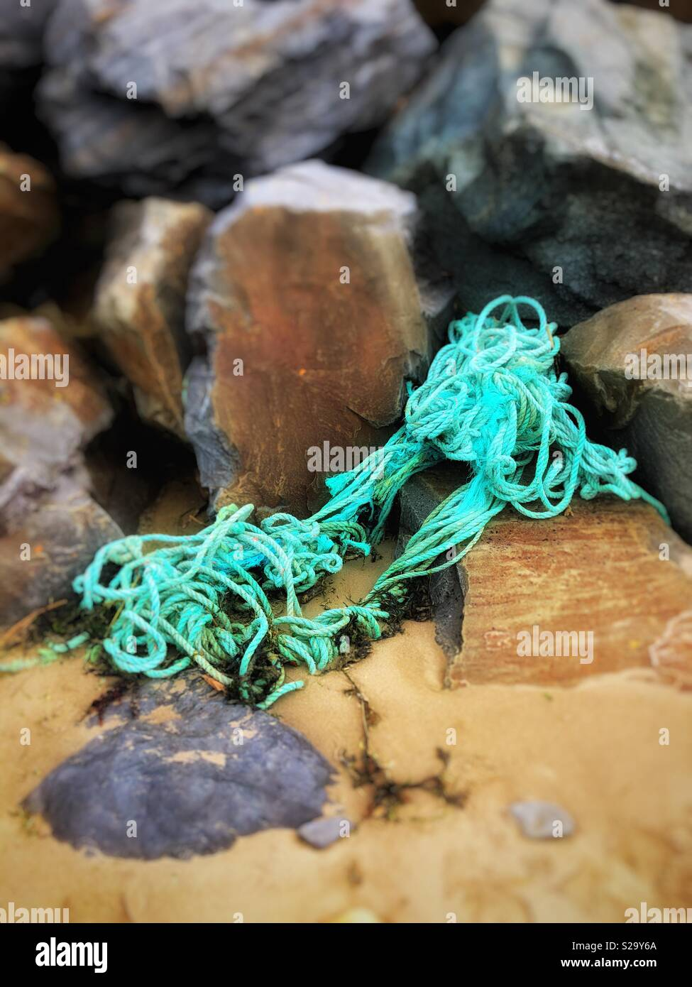 Fishing gear washed up on the high tide line of a Welsh beach. - Stock Image