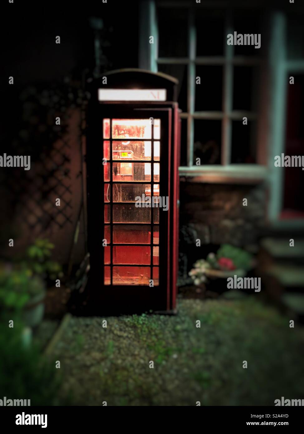 Old red telephone box in a remote Welsh village. - Stock Image