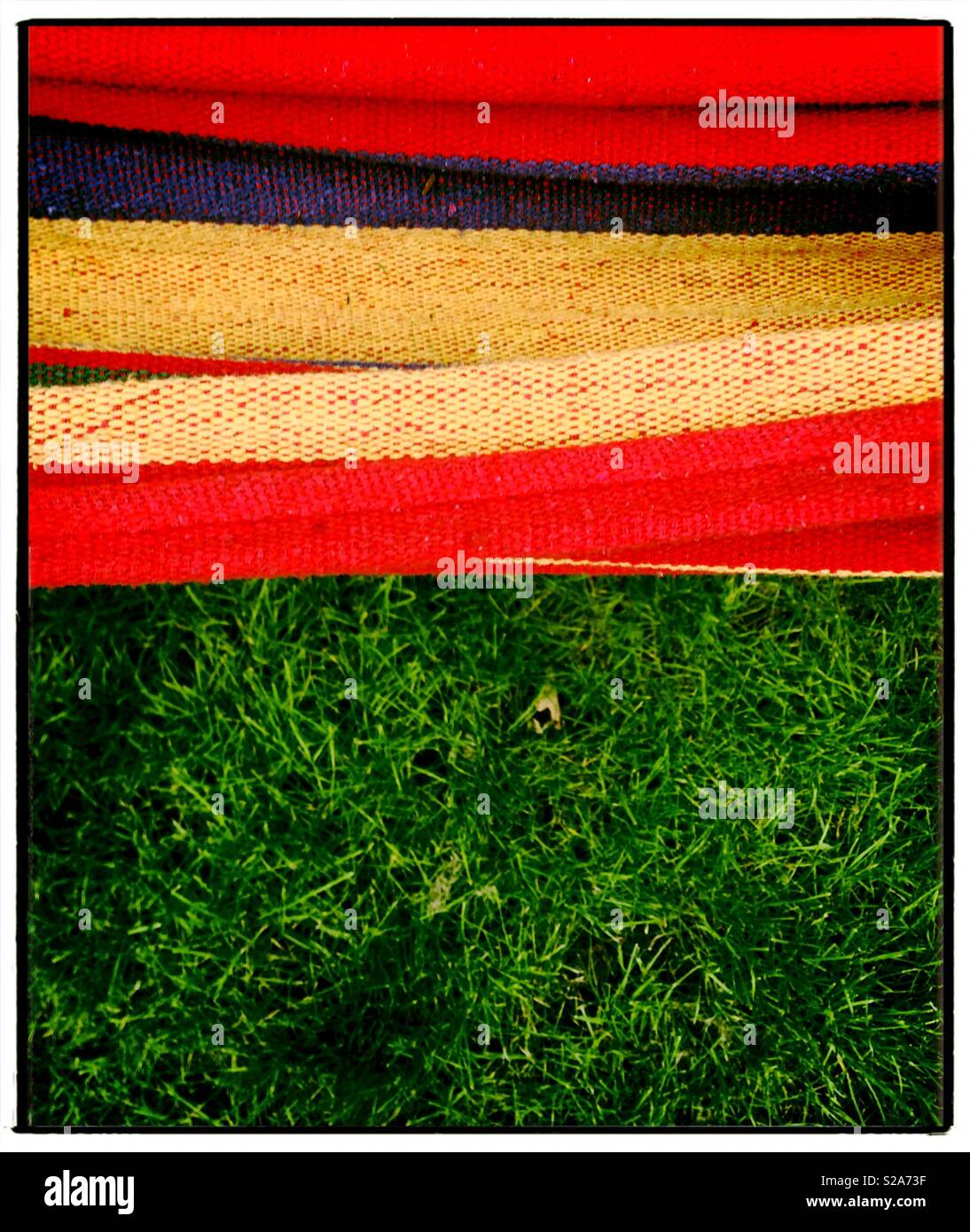 Colorful Stripy canvas with green lawn. - Stock Image