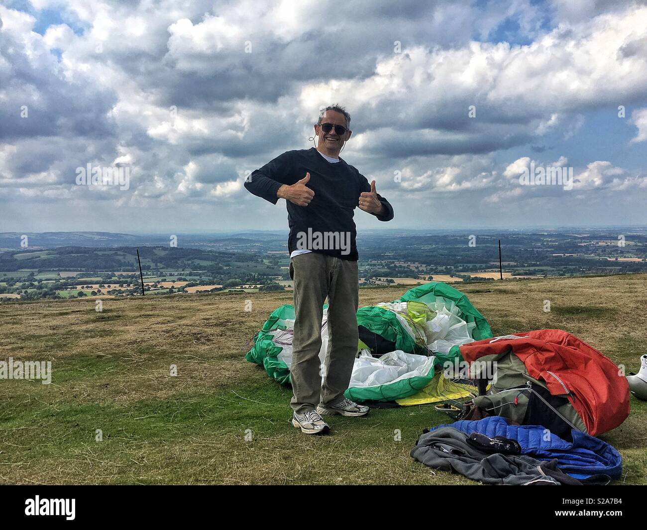 Man giving thumbs up after landing his paraglider Stock Photo