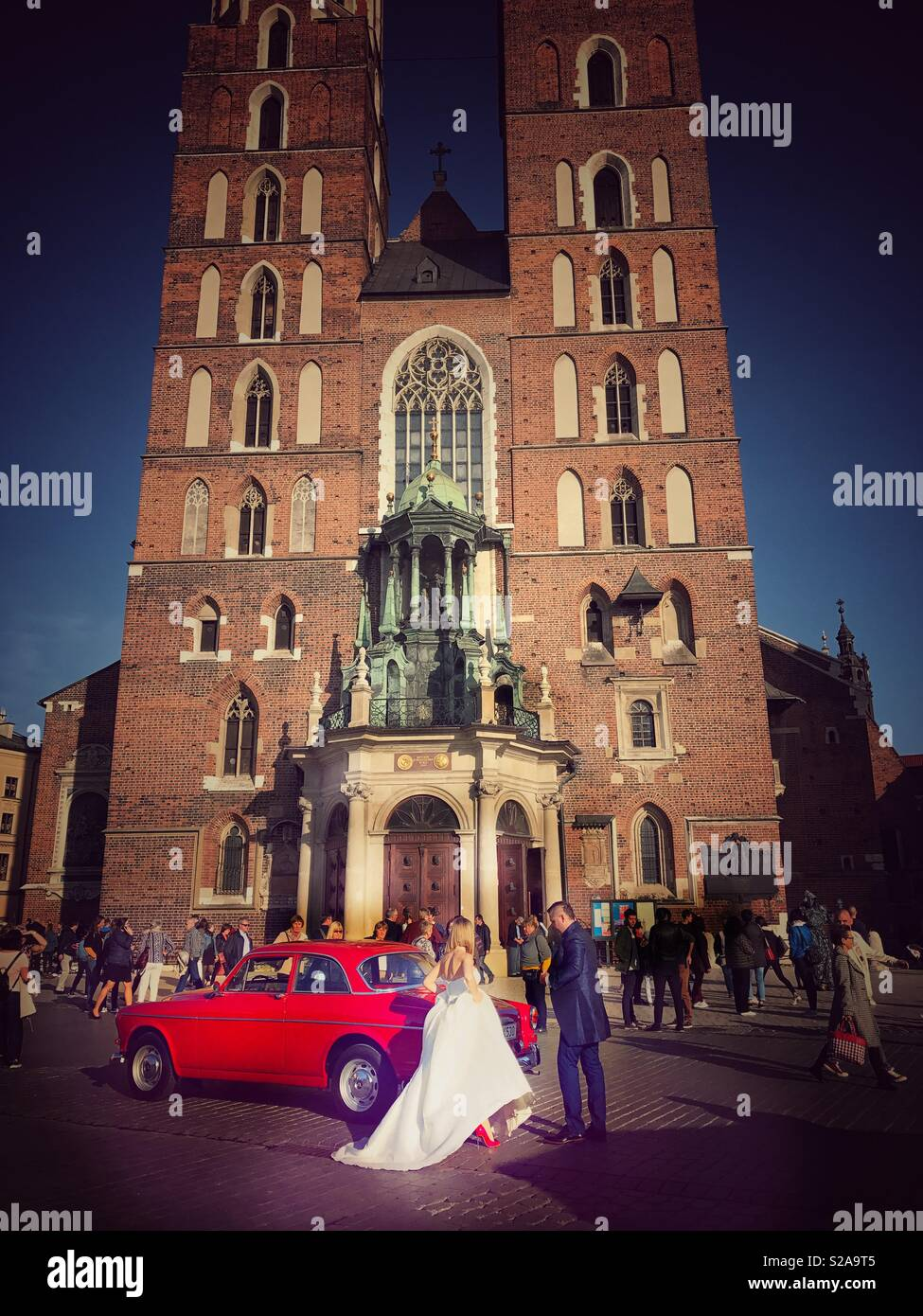 Bride in a white wedding gown and red stiletto shoes and groom in a tuxedo and a classic old red car in front of St. Mary's Basilica in Krakow, Poland - Stock Image