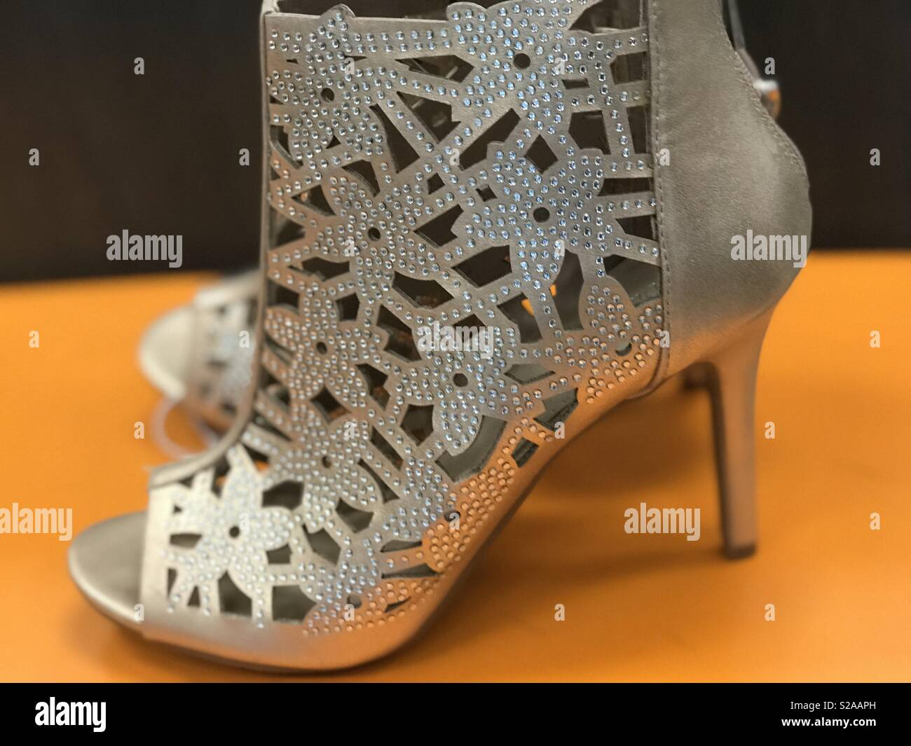 Gorgeous silver high heel shoes on a bright orange colored background - Stock Image