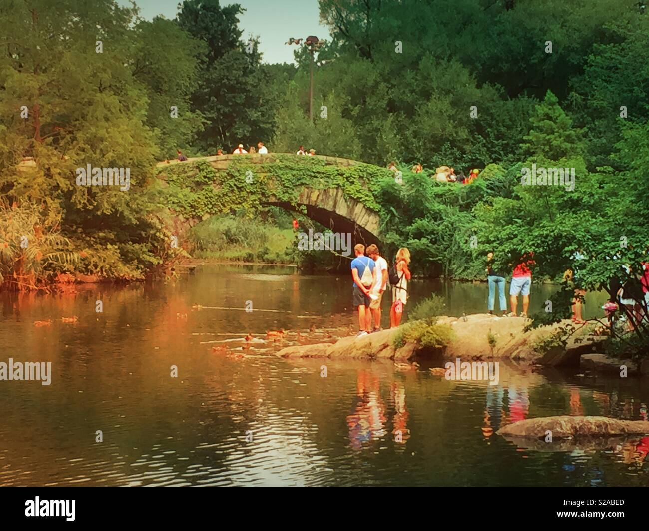 Tourists gather at the pond in front of Gapstow Bridge, Central Park, NYC, USA - Stock Image
