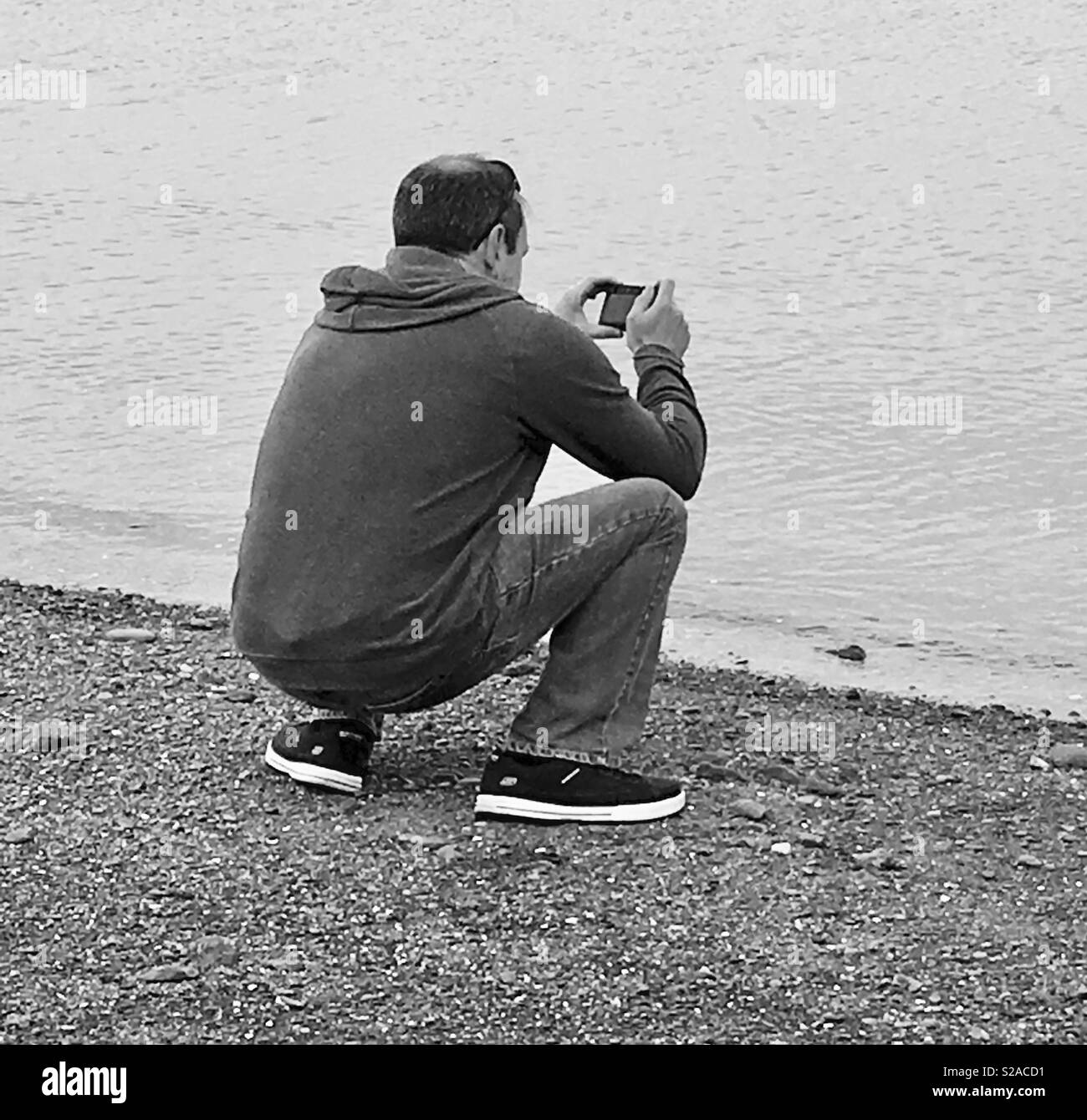 Man taking photos on the waters edge of a shingle beach - Stock Image