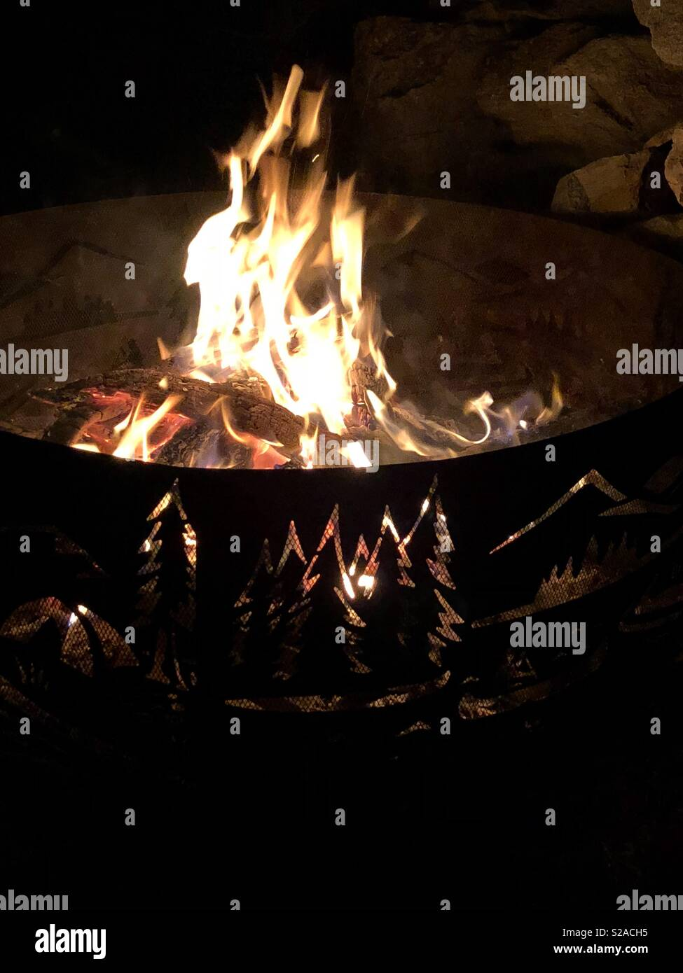 A campfire burns in a fire ring decorated with a cutout outdoor scene. - Stock Image