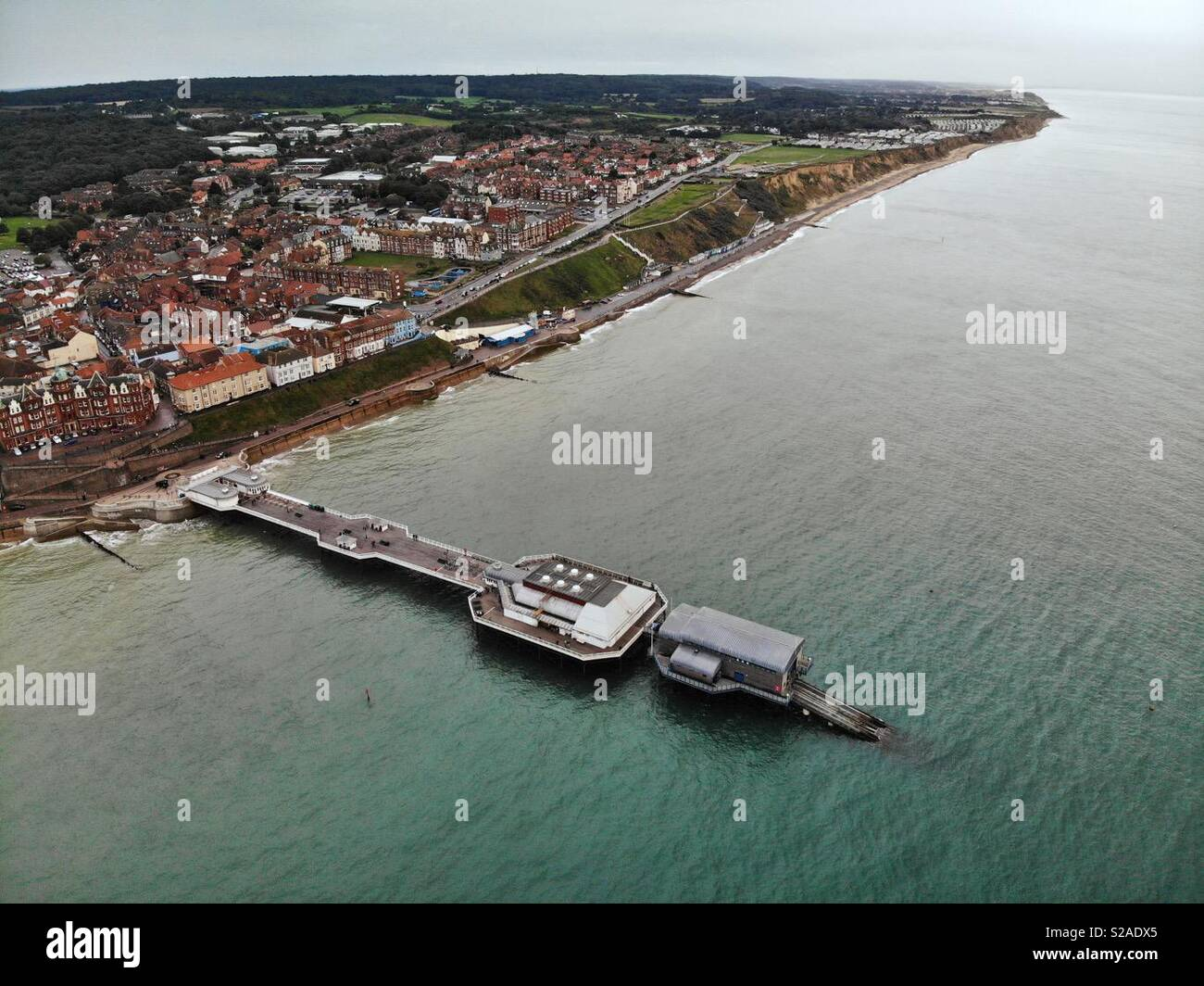 Aerial shot of Cromer pier from out to sea looking towards the town at dusk. - Stock Image