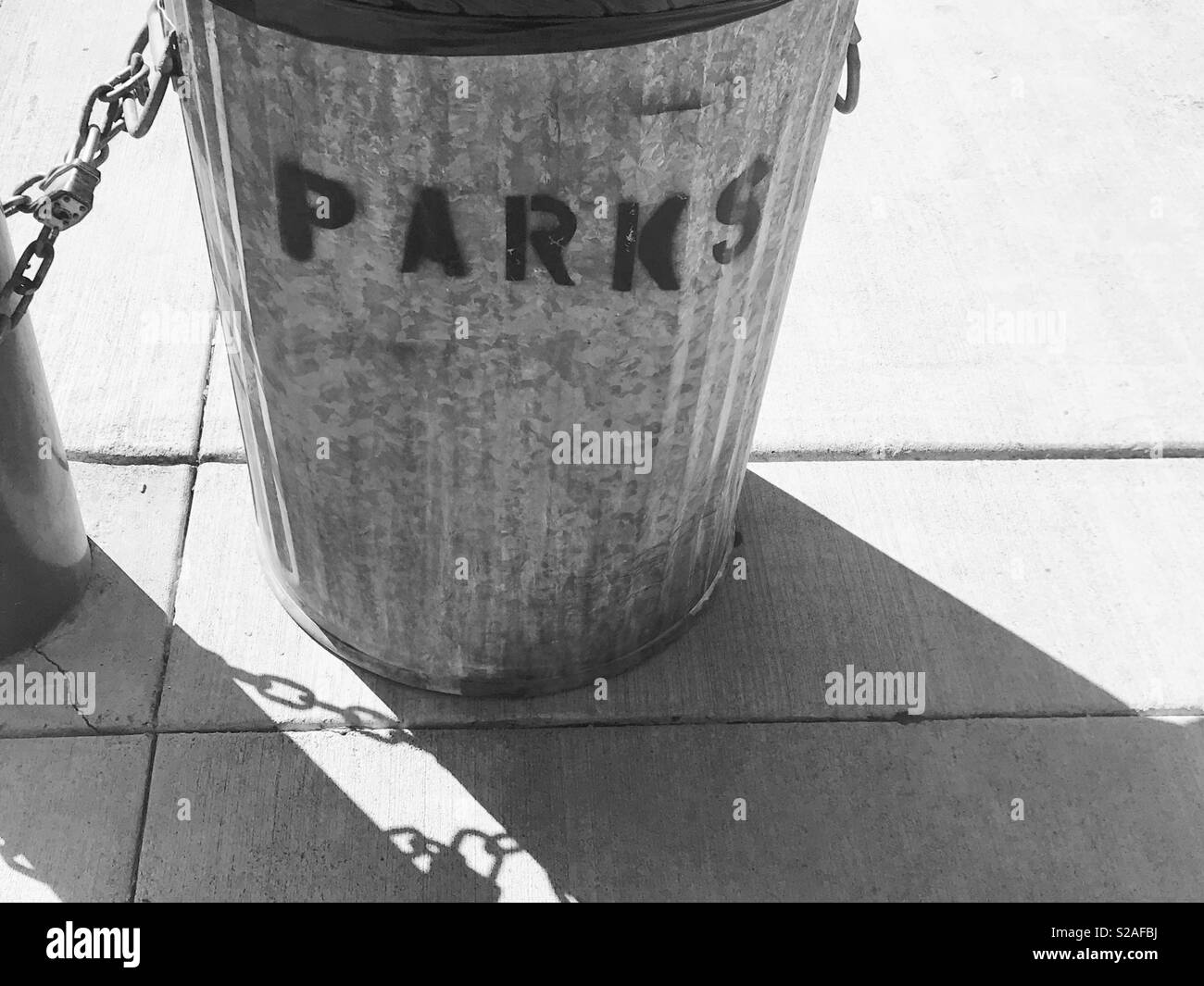 Garbage can at the park - black and white photograph- metal Garbage can spray painted on front with the word Parks - shadow photography - Stock Image