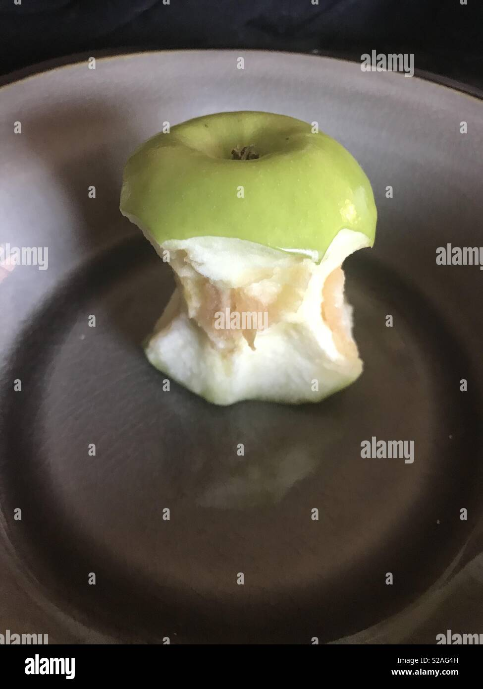 Picture of an old rotten Apple core sitting in s bowl - Stock Image