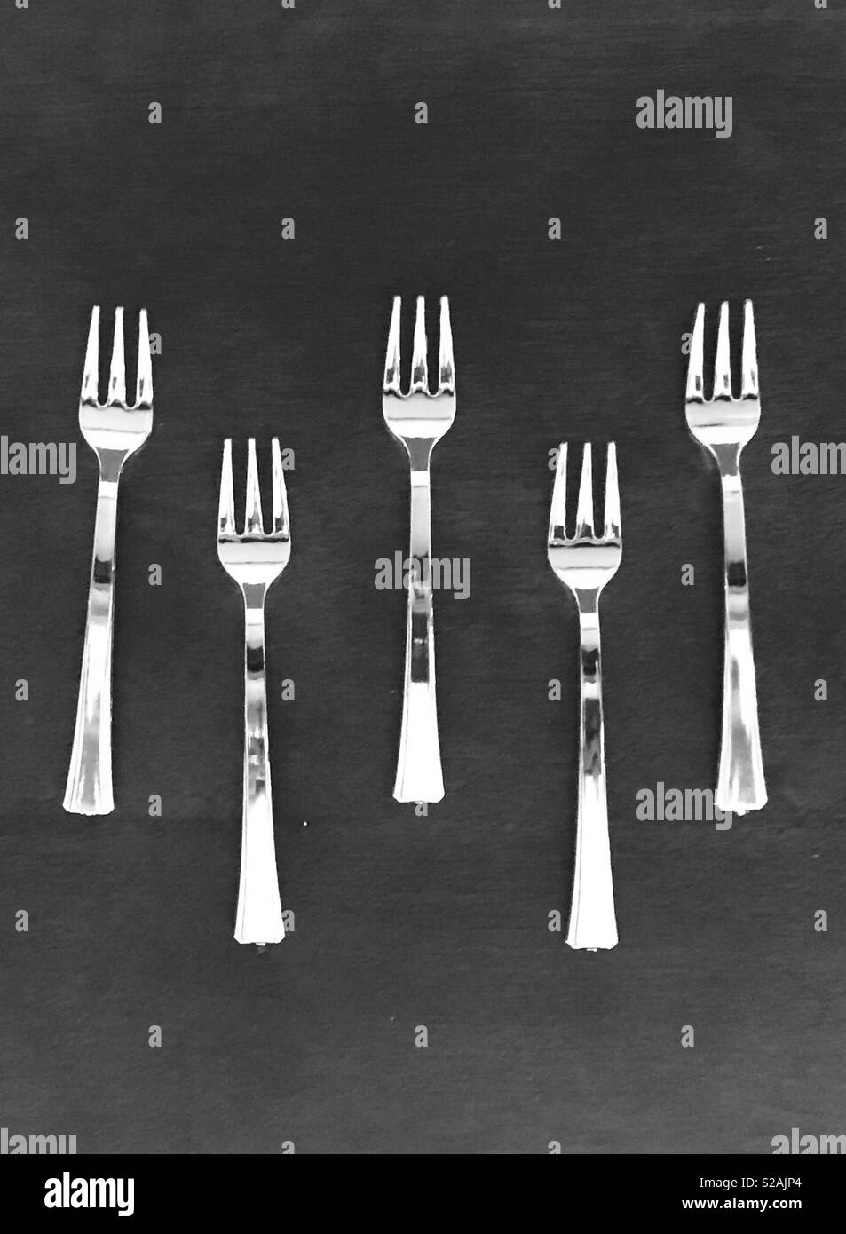 Silver shiny forks lined up in a row on a dark wooden back ground - Stock Image