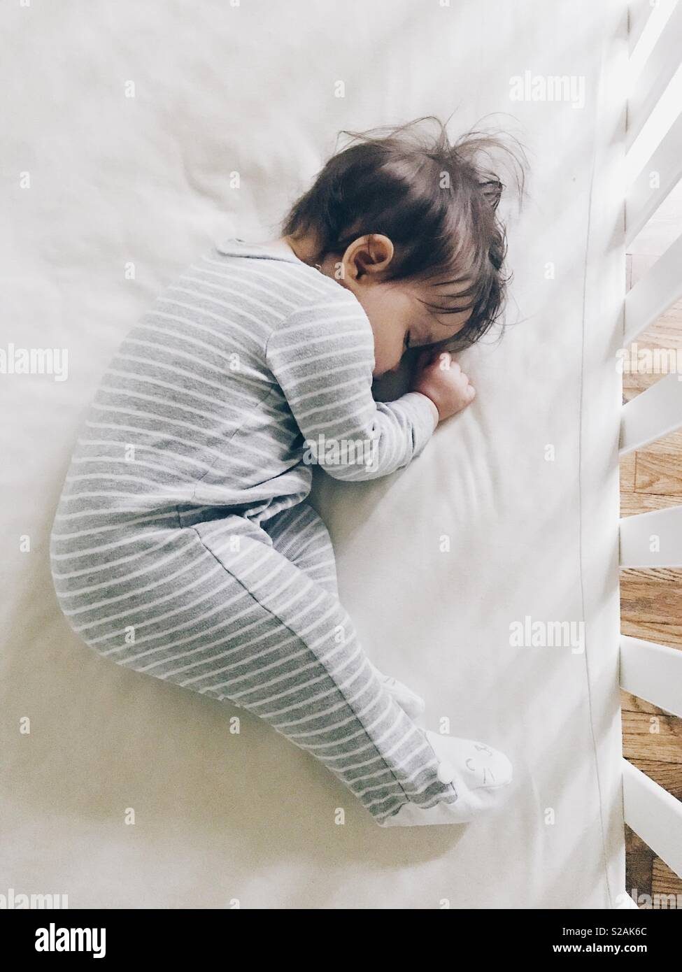 A young baby girl curled up asleep in her crib. - Stock Image