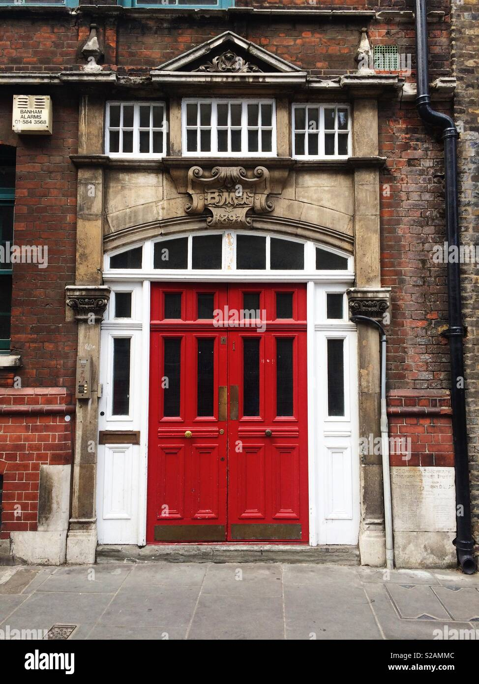 Red doors on an old brick building - Stock Image