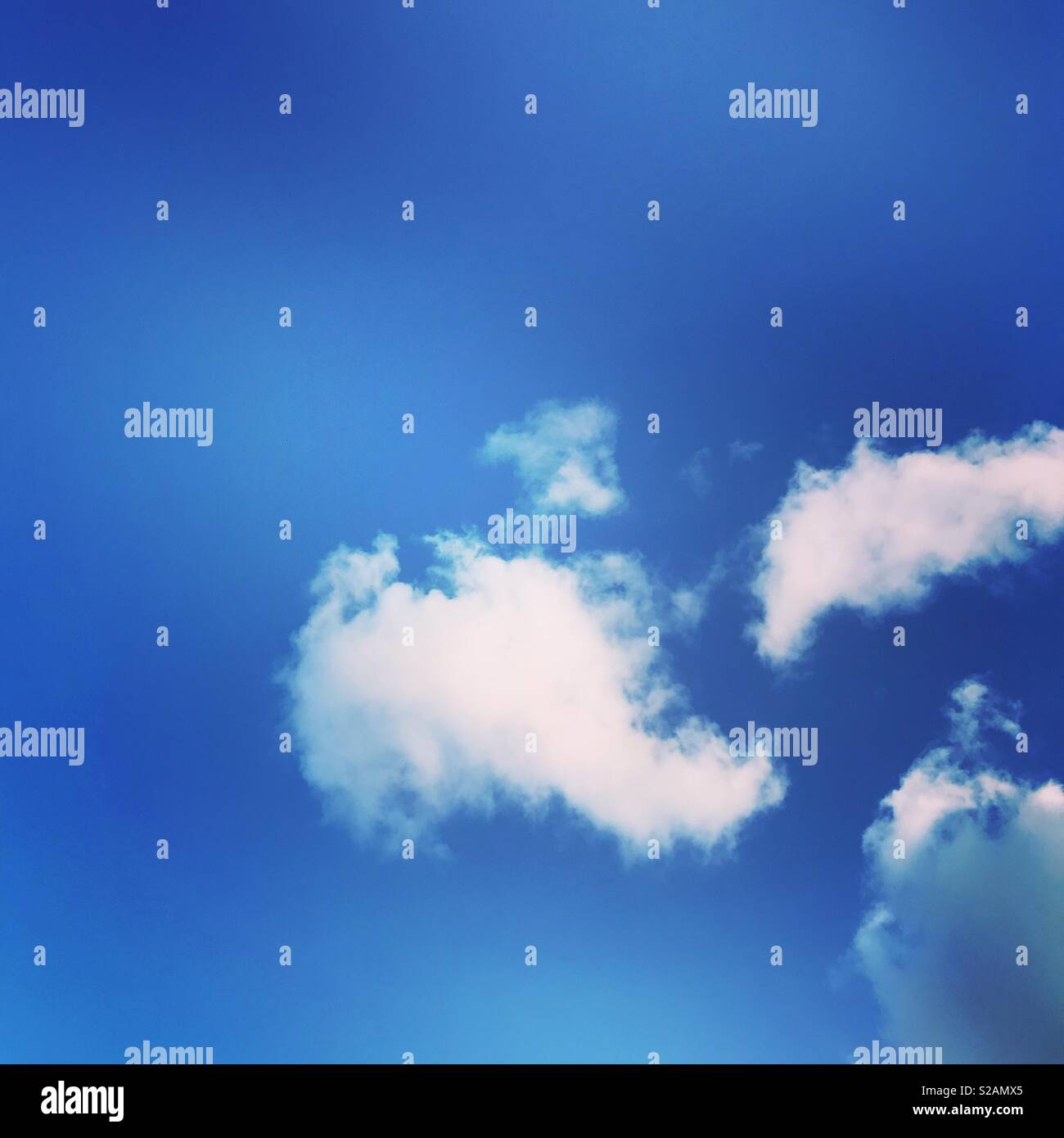 White fluffy clouds against a perfect blue sky - Stock Image