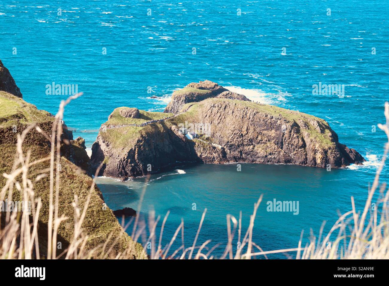 Carrick-a-Rede Rope Bridge spanning the dizzy gap between the mainland and a small island near Ballycastle Co. Antrim, Northern Ireland. - Stock Image