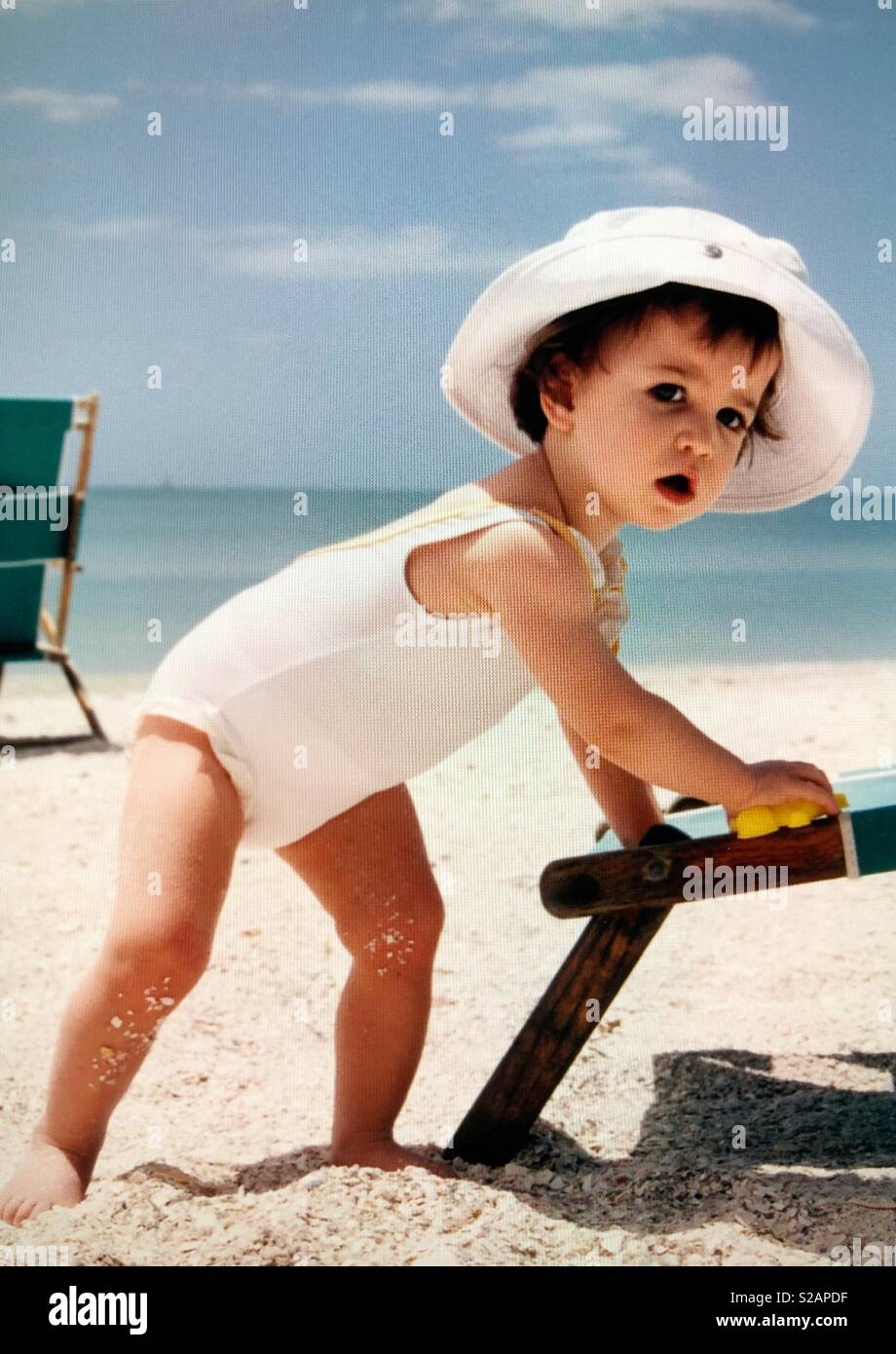 A toddler girl In a white bathing suit and hat plays in the sand on a beach - Stock Image