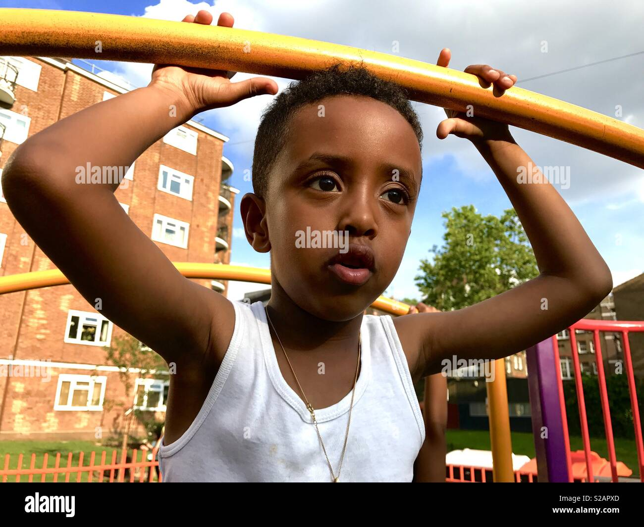 A good looking black boy with big eyes in a play ground wearing white vest - Stock Image