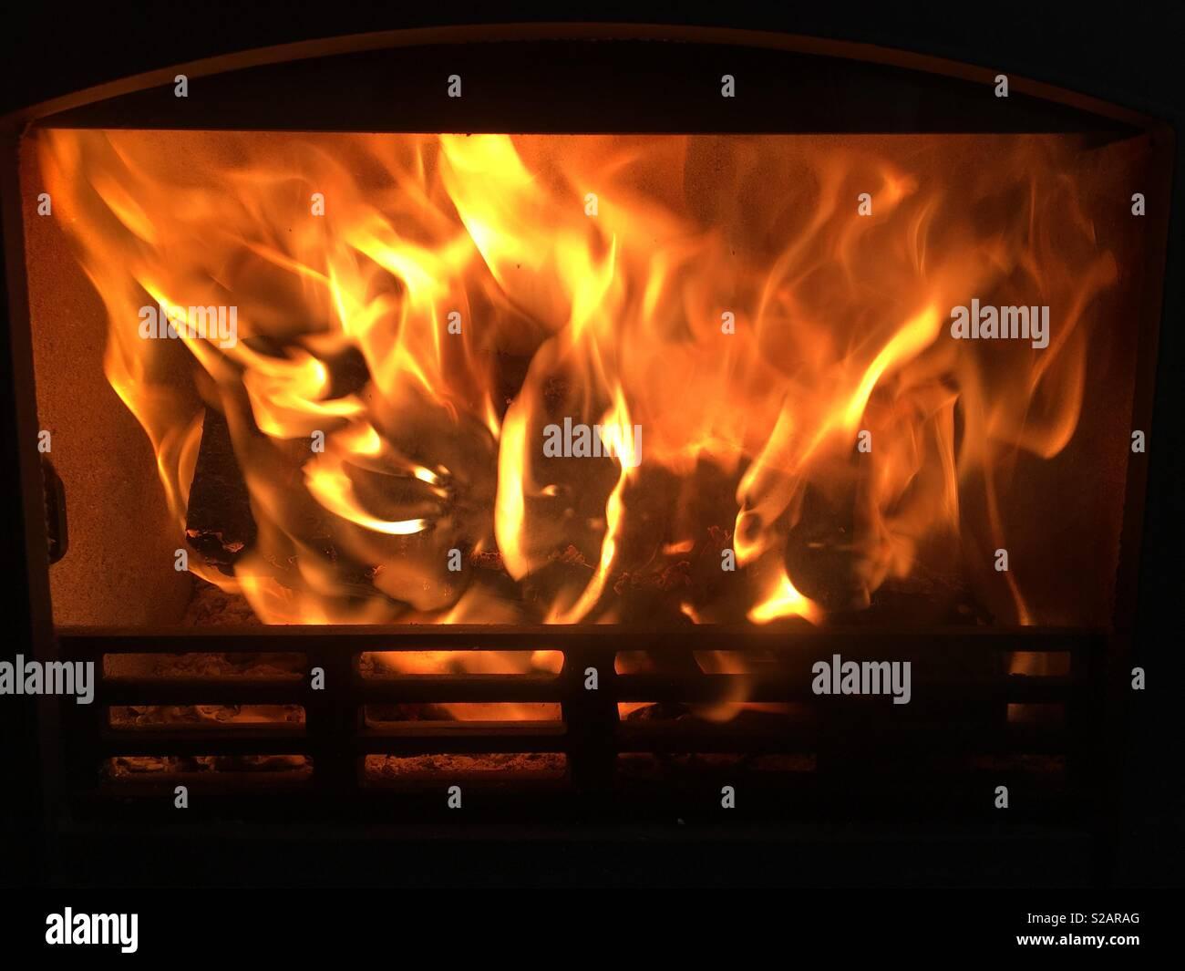 Fire burning fiercely in log burner close up - Stock Image