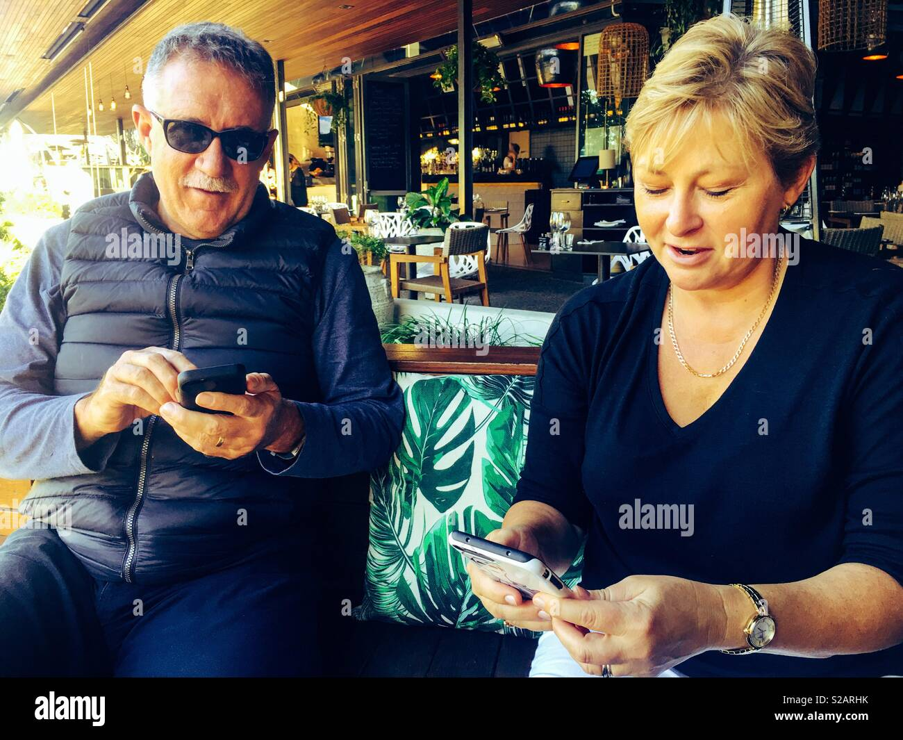 Fifty plus  male and female playing game on mobile phone is cafe At Southbank, Brisbane, Australia - Stock Image