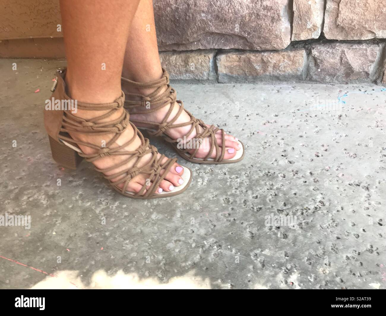 2255f77b88962 Natural sunlight shining on a woman s feet while wearing strappy gladiator sandals  with straps outside on