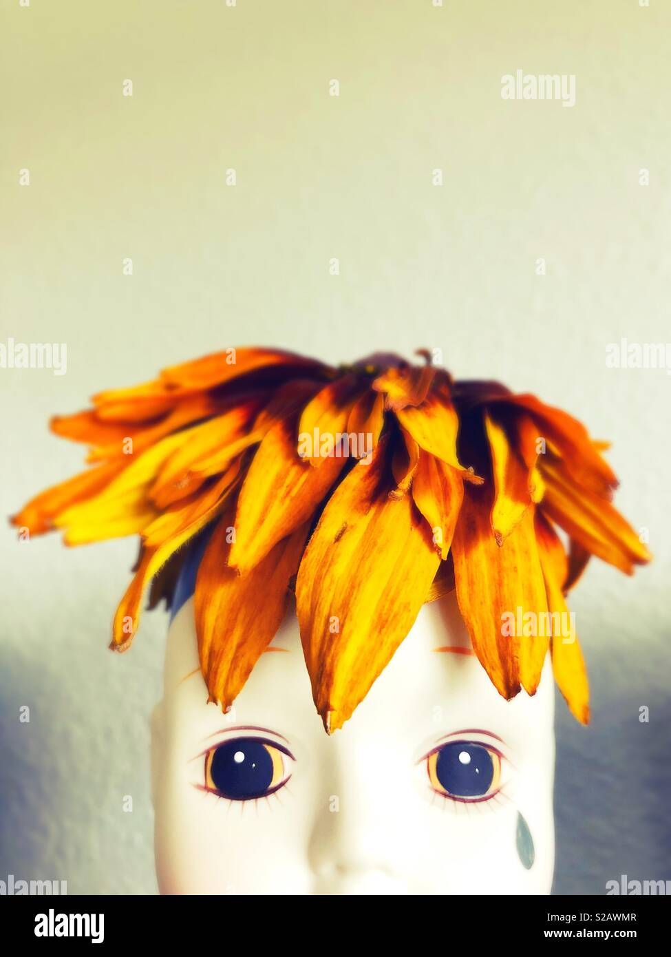 Doll head with real flower hat. - Stock Image