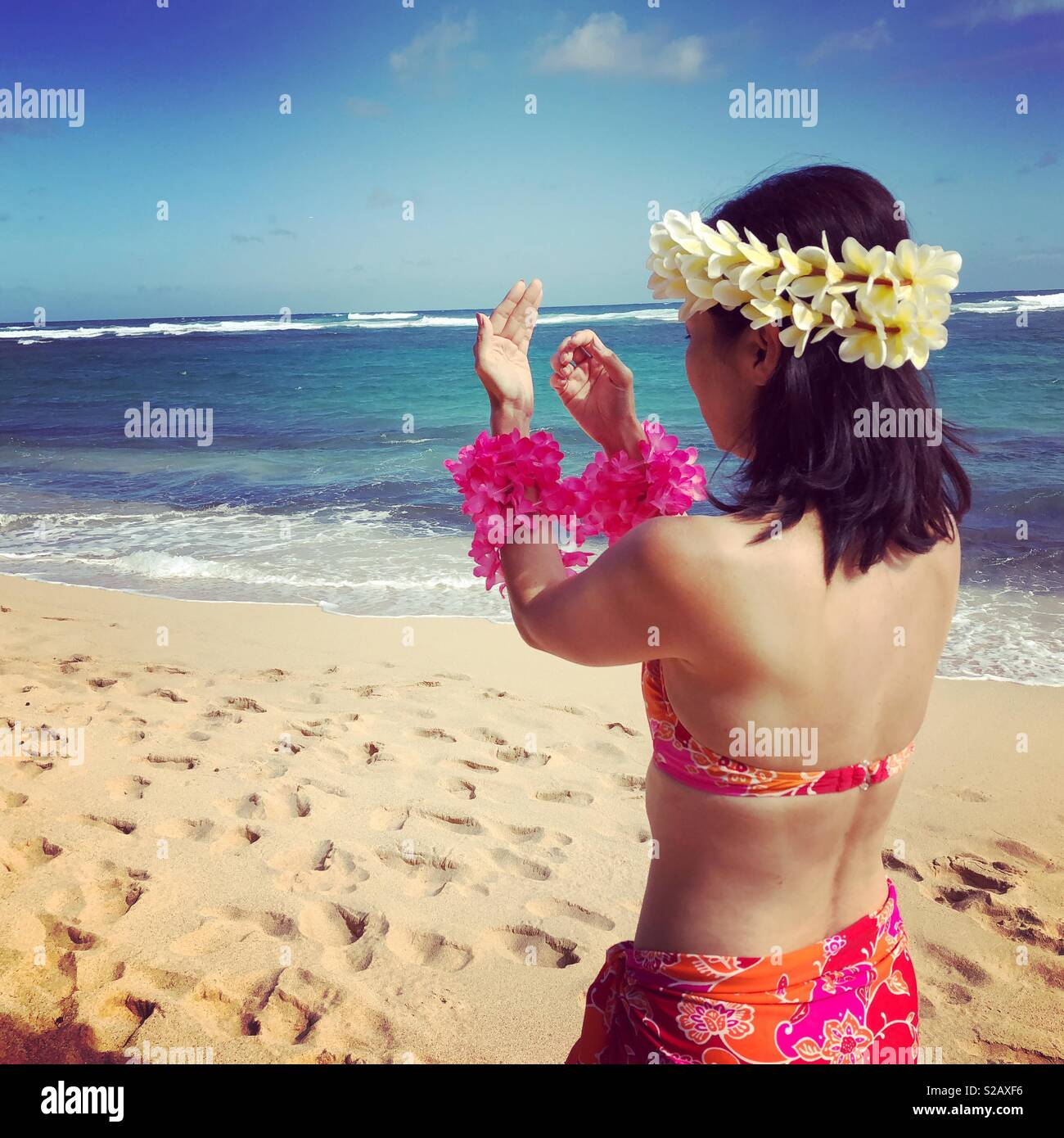 Hawaiian hula girl in pink bikini and pareo sarong gestures aloha island love on a wide expanse of tropical island beach wearing traditional lei of hibiscus and plumeria - Stock Image