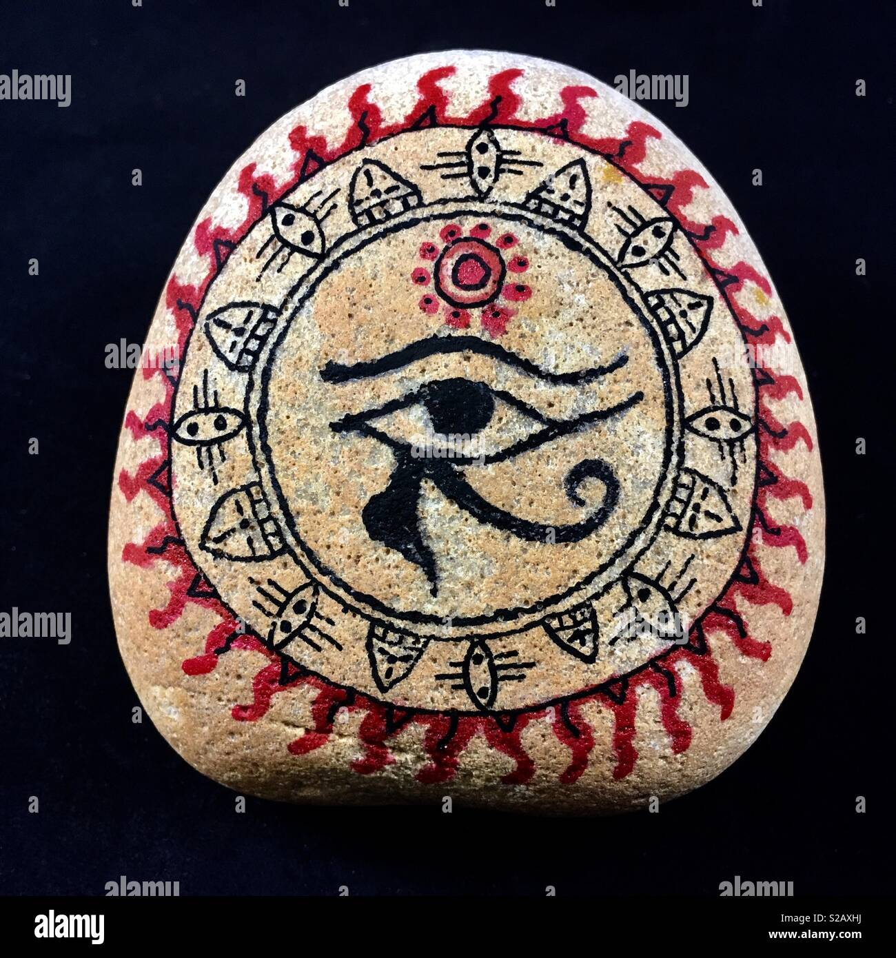 Egyptian tribal art sun god Ra, painted on sandstone. - Stock Image