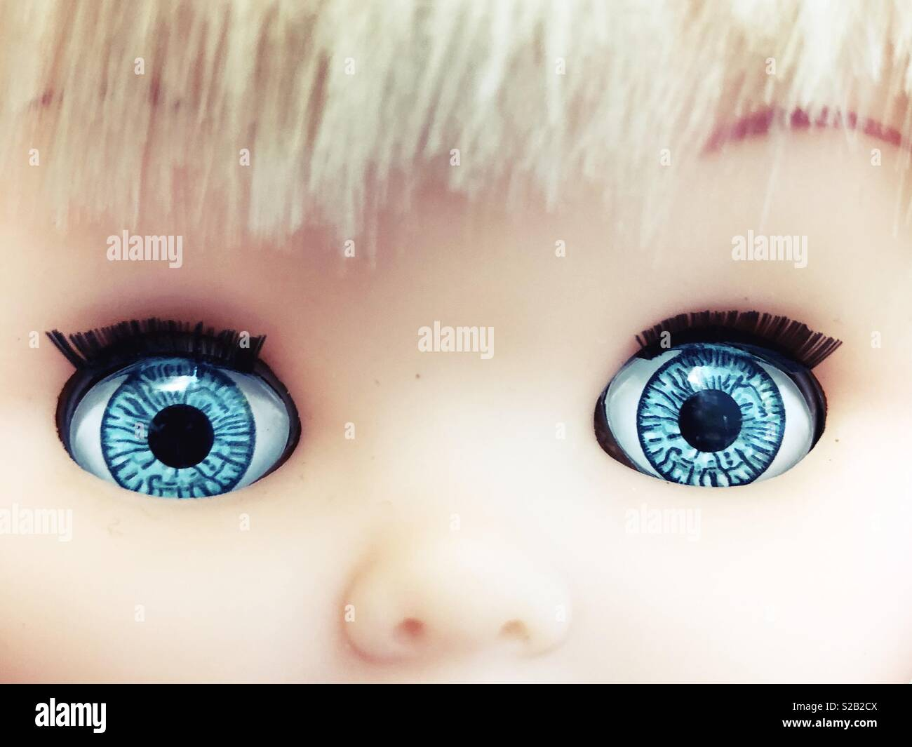 Close up of a doll's big blue eyes. - Stock Image