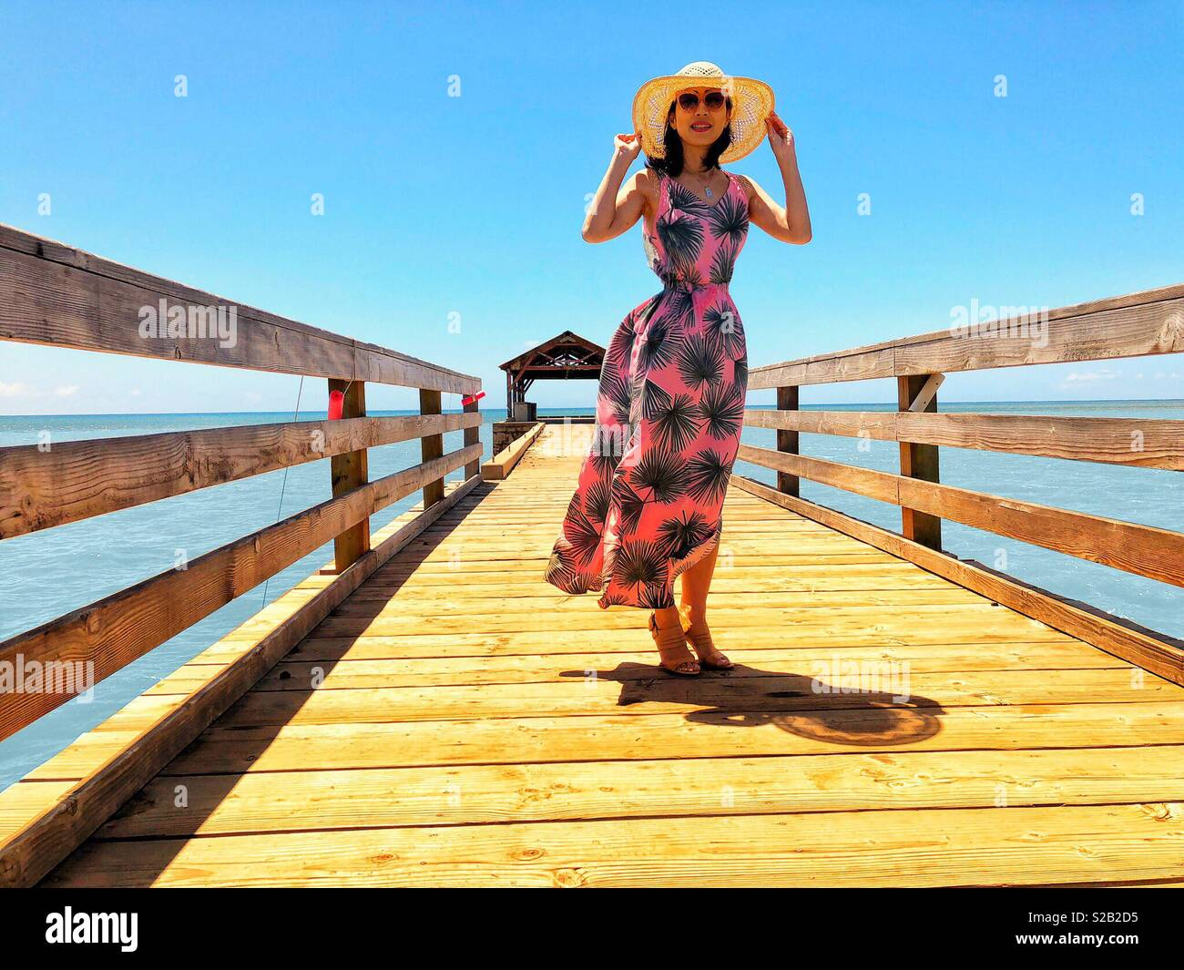 Beautiful young brunette woman with shapely figure, long floral pink and green sundress, pink sunglasses and sun hat smiling glowingly aboard a long fishing pier in tropical Waimea Kauai Hawaii. - Stock Image