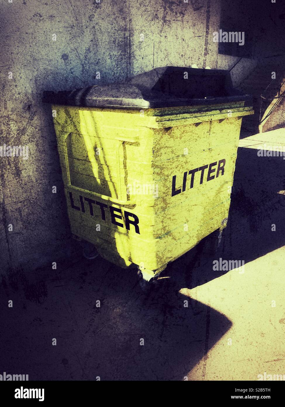 Yellow, plastic dumpster with black lid and bold black lettering - Stock Image