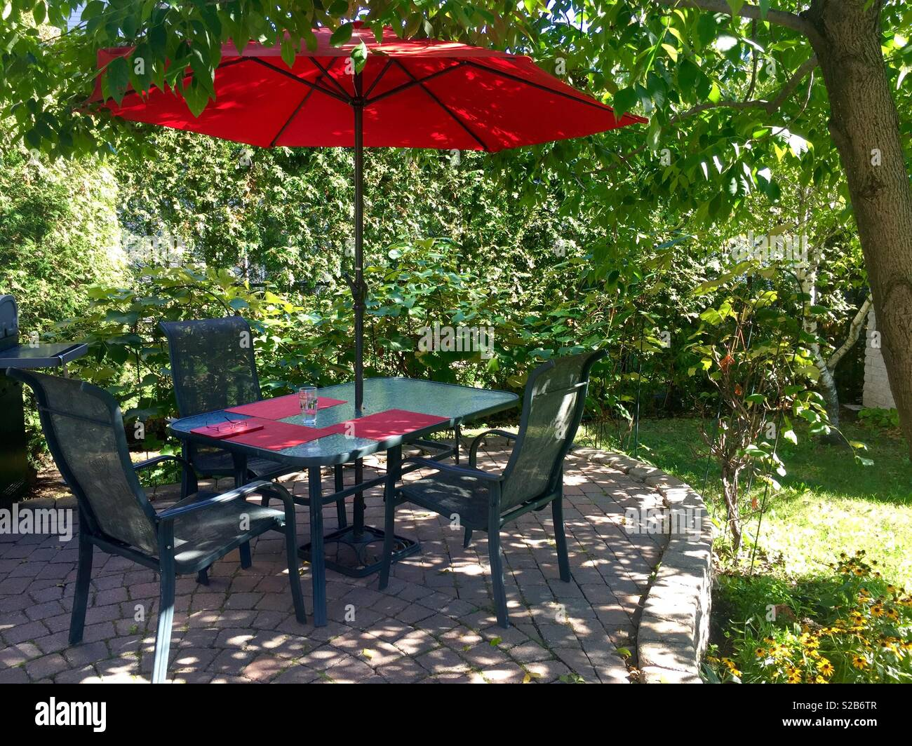 Patio Table With Red Umbrella And Three Chairs On The Patio In The