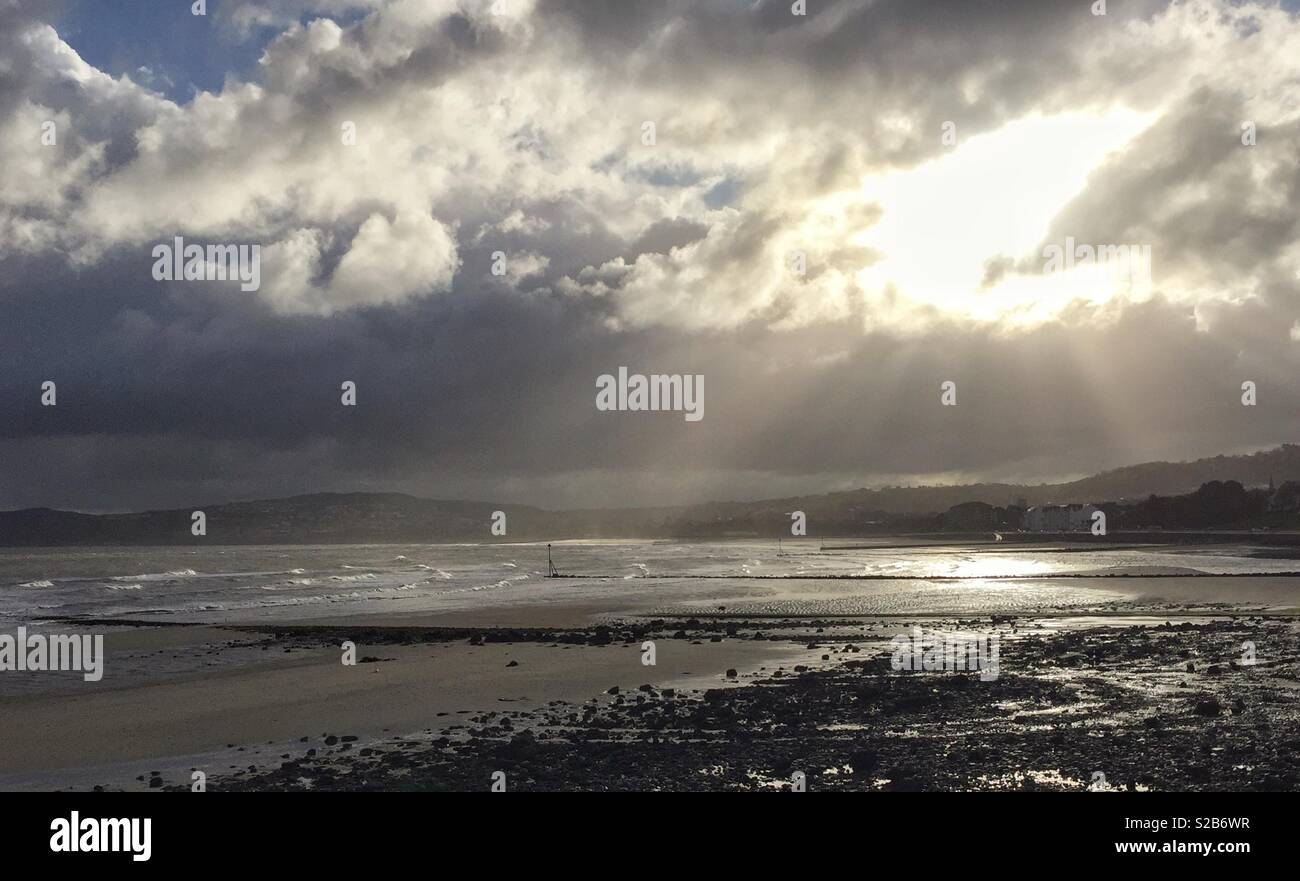 Sun rays bursting through clouds at Rhos-on-Sea in North Wales Stock Photo