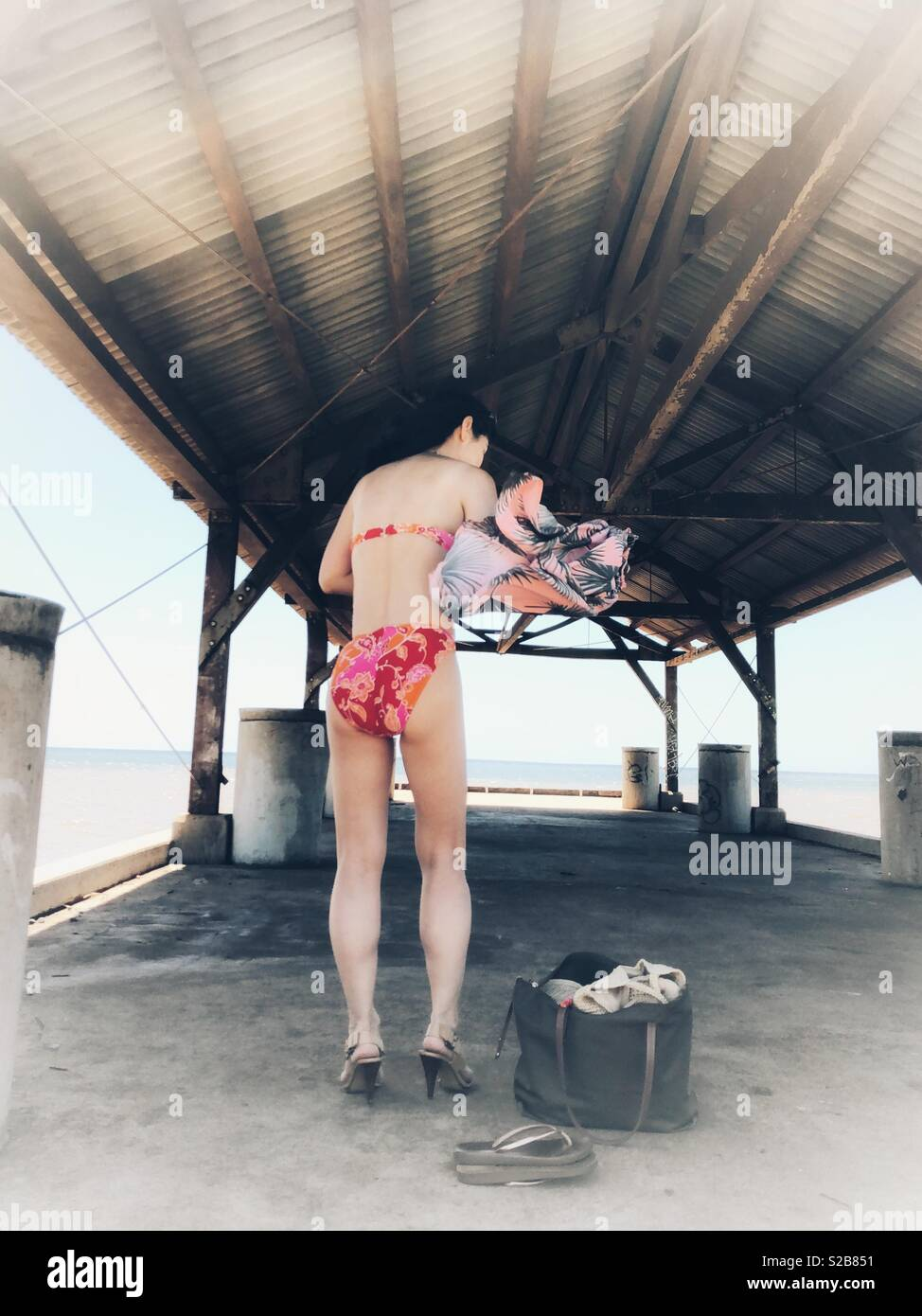Brunette girl, young woman, in high heels changing clothes from sundress to floral pink bikini on a covered fishing pier in Hawaii Stock Photo