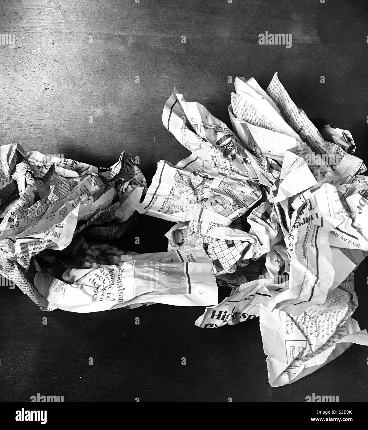 Black and white photo of crumpled up newspaper laying on a dark brown hardwood table - Stock Image
