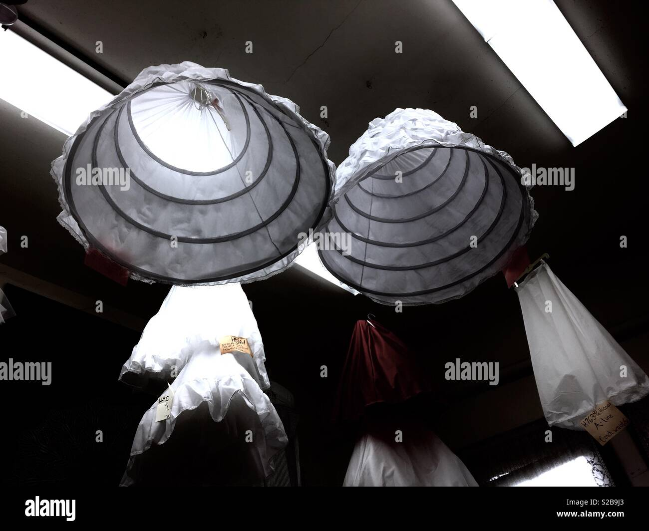 Hoop skirts hanging from the ceiling. - Stock Image