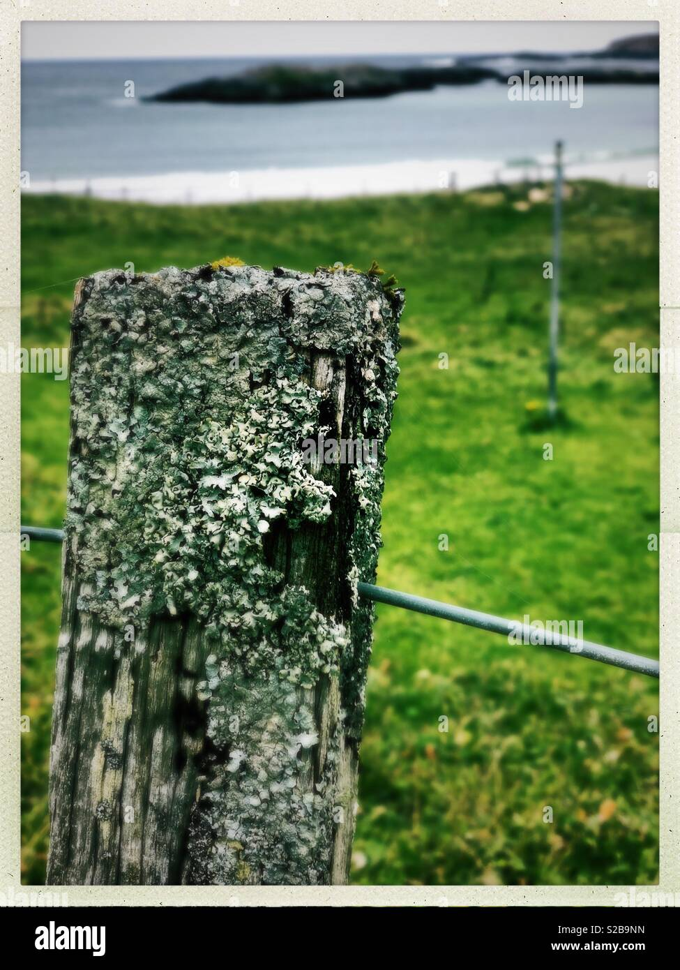 Weathered fence post looking on to island in small Western Isles Bay in Scotland in September - Stock Image