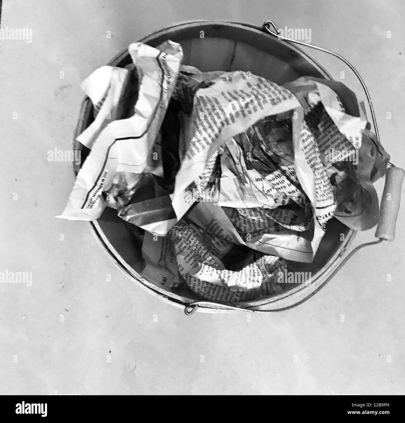 Black and white photo of Newspapers crumpled up in a basket - Stock Image
