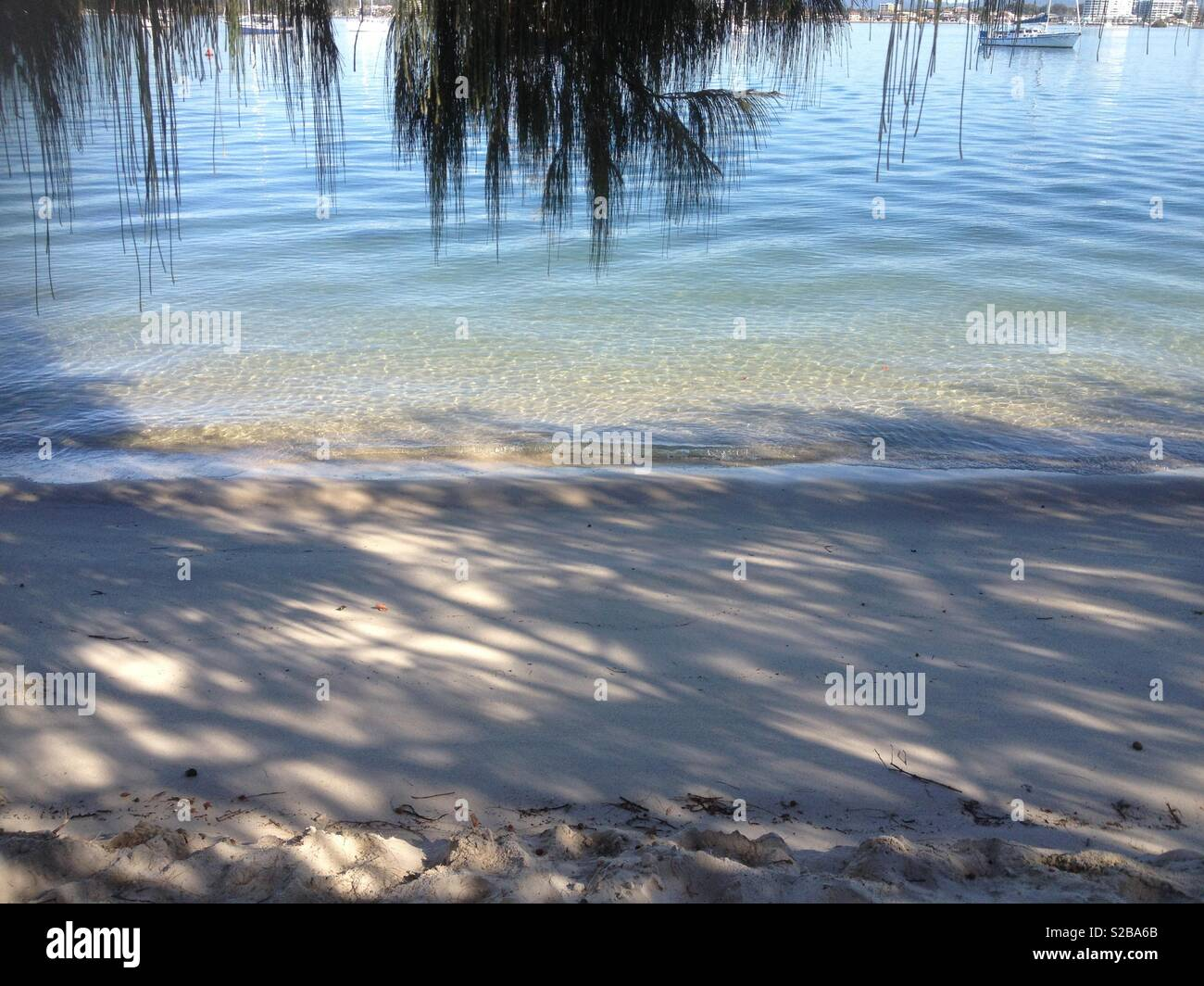 Tranquil, shaded beach with gentle waves and flat, calm blue water - Stock Image