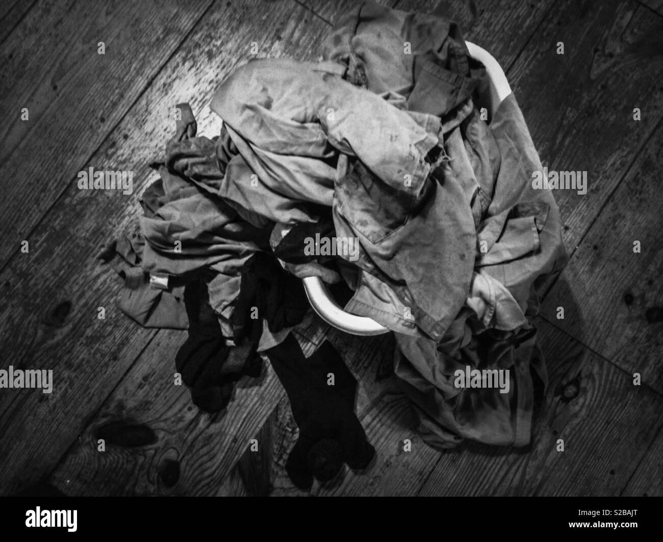 Black and white photo of dirty laundry spilling over laundry basket- beauty in the mundane- viewed from above - Stock Image