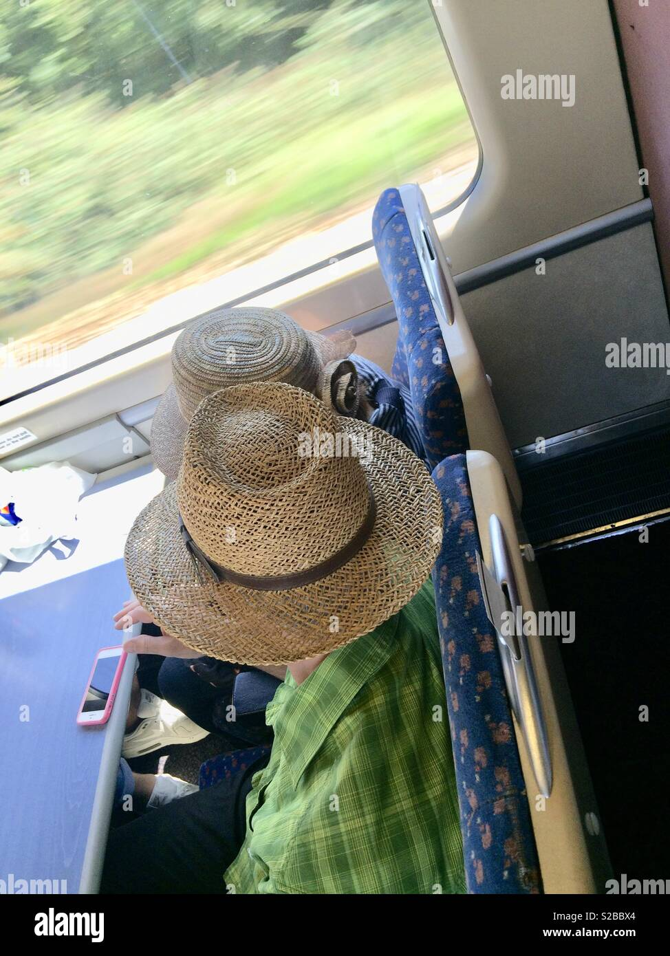 Couple with summer hats sitting in a fast train - Stock Image